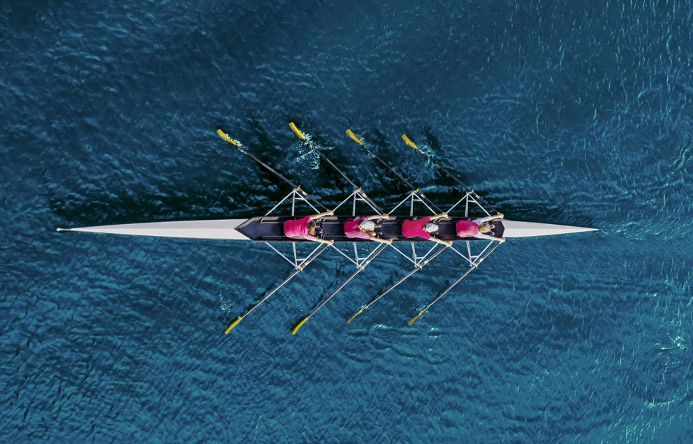 Women's Rowing Team On Blue Water
